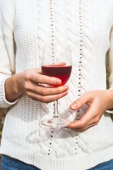 Ein glas roter hauptwein in den händen einer frau in einer weißen strickjacke.