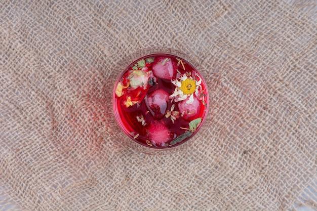 Ein glas roter saft auf sackleinen mit blumen. foto in hoher qualität