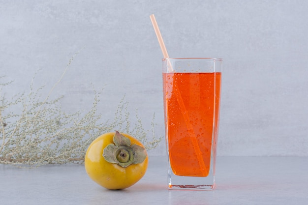 Ein glas roter saft mit kaki auf steinhintergrund. foto in hoher qualität
