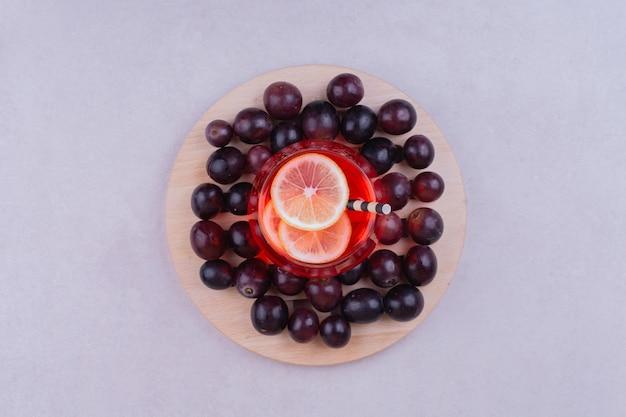 Ein glas roter saft mit kirschbeeren auf einem holzbrett