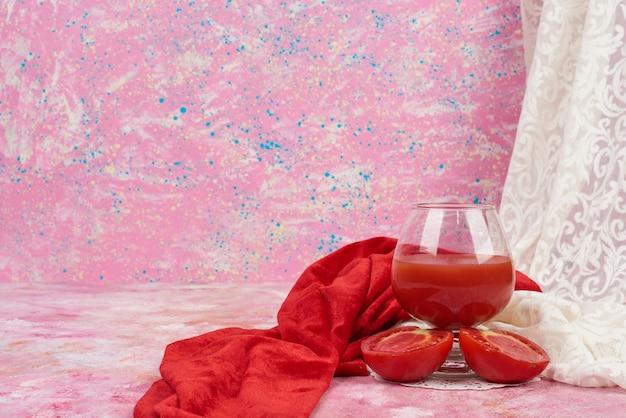 Ein glas roter saft mit tomaten herum.