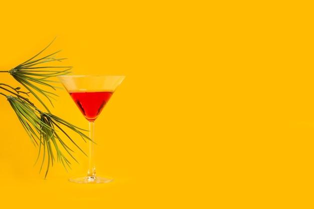 Ein glas roter wermut auf gelbem grund