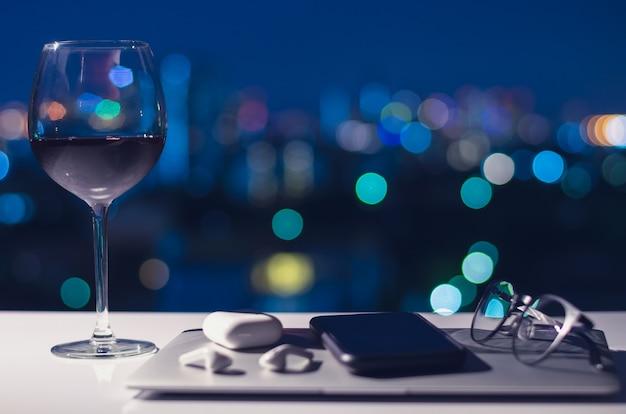 Ein glas rotwein auf den tisch stellen, um nach dem ausschalten von laptop, smartphone und kopfhörer zu genießen.