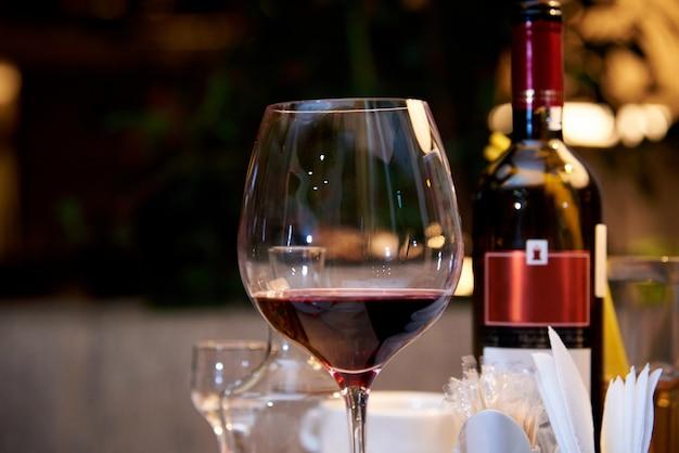 Ein glas rotwein auf einem gedienten tisch in einem restaurant.