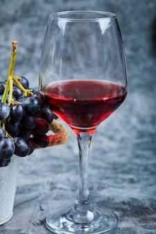 Ein glas rotwein auf einem marmorhintergrund mit trauben. hochwertiges foto