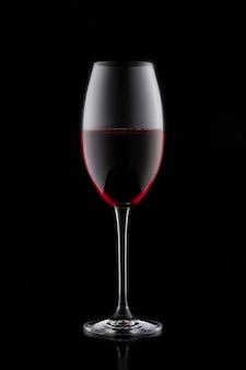 Ein glas rotwein auf einem schwarzen hintergrund.