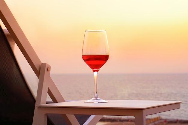 Ein glas rotwein auf einem sonnenuntergangseehintergrund. romantisches datumskonzept