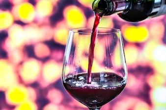 Ein Glas Rotwein gießen