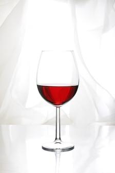 Ein glas rotwein in bordeaux-form auf hellem hintergrund