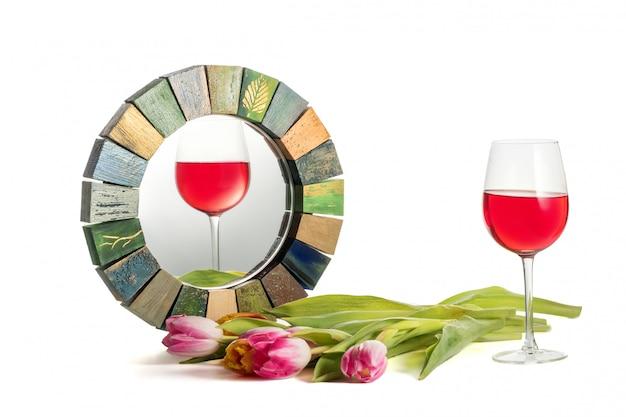 Ein glas rotwein mit geneigtem horizont spiegelt sich korrekt im handgemachten spiegel wider