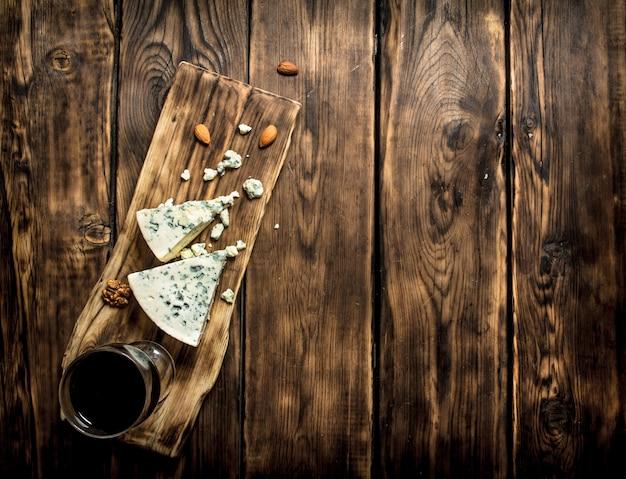 Ein glas rotwein mit italienischem käse mit blauschimmel.