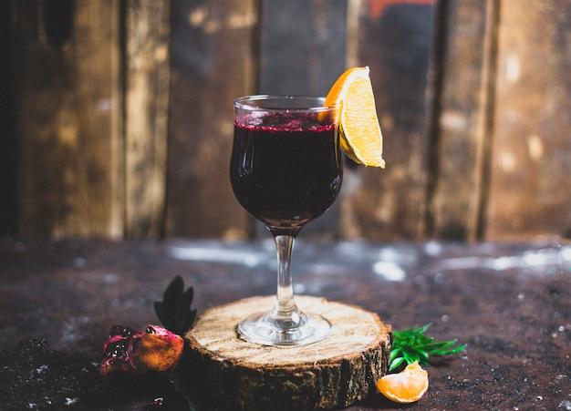 Ein glas rotwein mit zitronenscheibe, orange auf einem stück holz