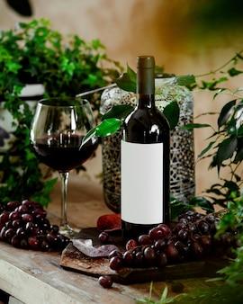 Ein glas rotwein und eine flasche rotwein auf dem tisch mit roten trauben