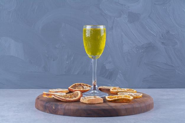 Ein glas saft, getrocknete orangen- und zitronenscheiben an bord auf marmortisch.
