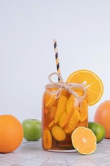 Ein glas saft mit fruchtscheiben und frischen früchten an der weißen wand.