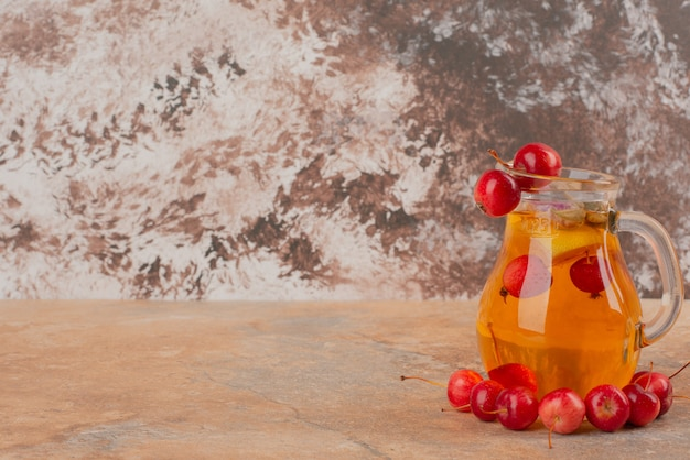 Ein glas saft mit kirschäpfeln auf marmortisch dekoriert.
