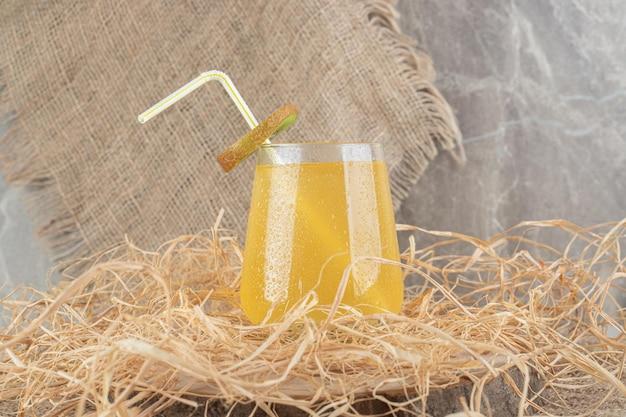 Ein glas saft mit kiwischeibe und stroh auf sackleinen