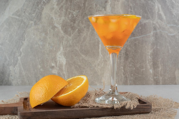 Ein glas saft mit zitrusfrüchten auf holzbrett
