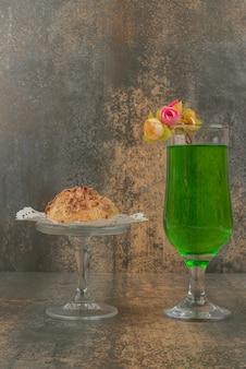Ein glas saftige grüne limonade und ein stück kuchen auf weißem teller