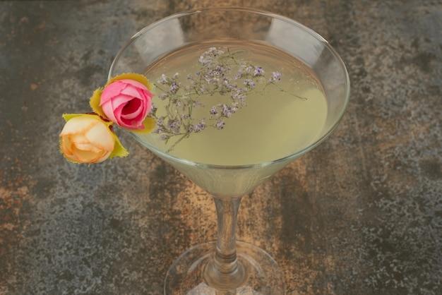 Ein glas saftige limonade und rosen auf marmoroberfläche.
