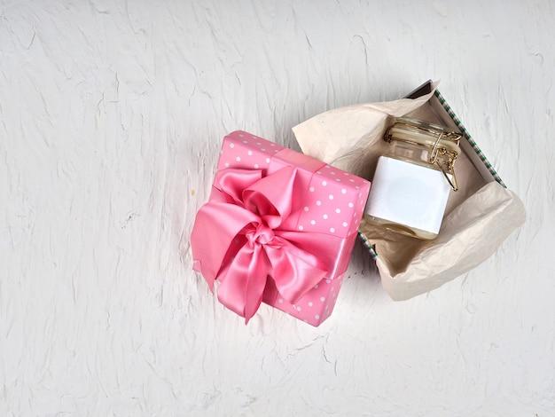 Ein glas sahne, lotion leeres etikett in einer schachtel mit einem rosa band.