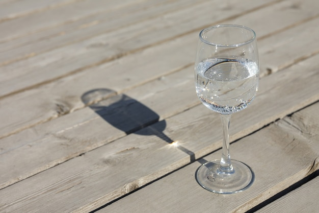 Ein glas sauberes sprudelwasser steht auf einem grauen holzboden aus alten brettern. die vorteile von mineralwasser.