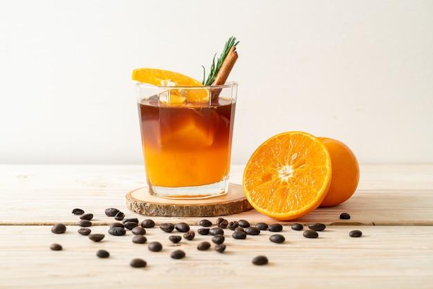 Ein glas schwarzer americano-eiskaffee und eine schicht orangen- und zitronensaft, dekoriert mit rosmarin und zimt auf einem holztisch