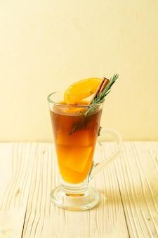 Ein glas schwarzer americano-eiskaffee und eine schicht orangen- und zitronensaft, dekoriert mit rosmarin und zimt