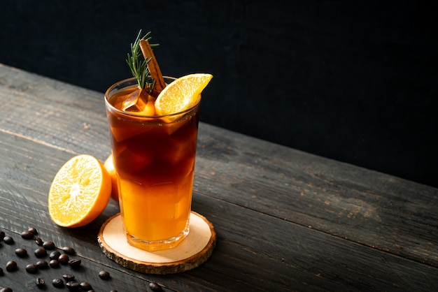 Ein glas schwarzer americano-eiskaffee und eine schicht orangen- und zitronensaft, dekoriert mit rosmarin und zimt Premium Fotos