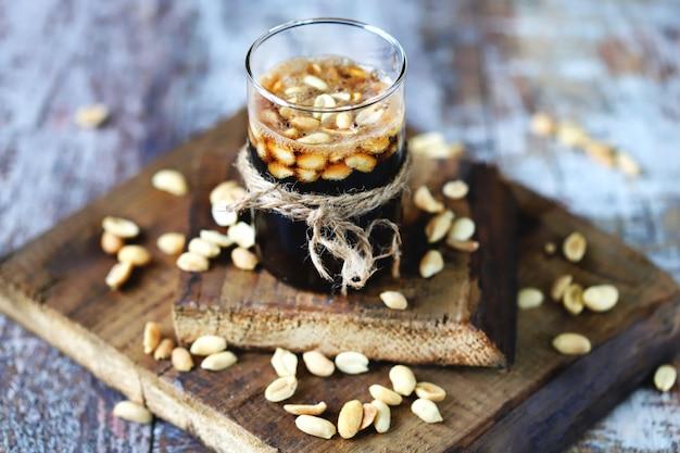 Ein glas schwarzes limonadengetränk und erdnüsse. gesalzene erdnüsse in einem glas mit cola. amerikanisches essen.