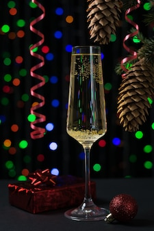 Ein glas sekt und ein weihnachtsbaum auf einer bokeh-oberfläche