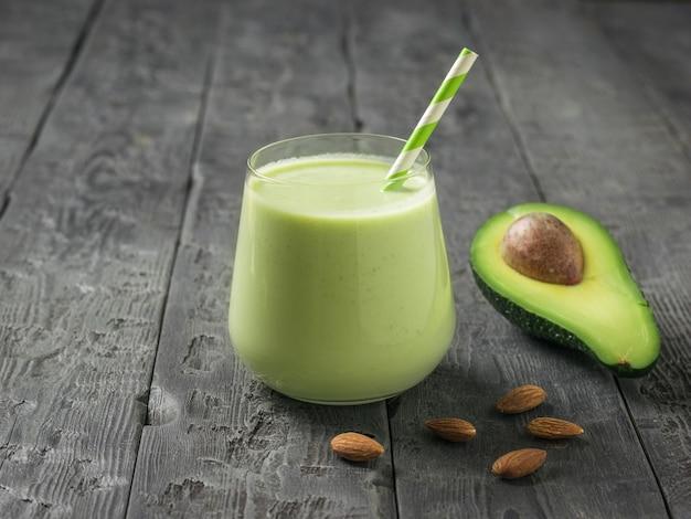 Ein glas smoothies und eine cocktailröhre und avocado auf einem holztisch. fitnessprodukt. diätetische sporternährung.