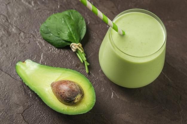 Ein glas spinat und avocado auf einem steintisch. fitnessprodukt. diätetische sporternährung.
