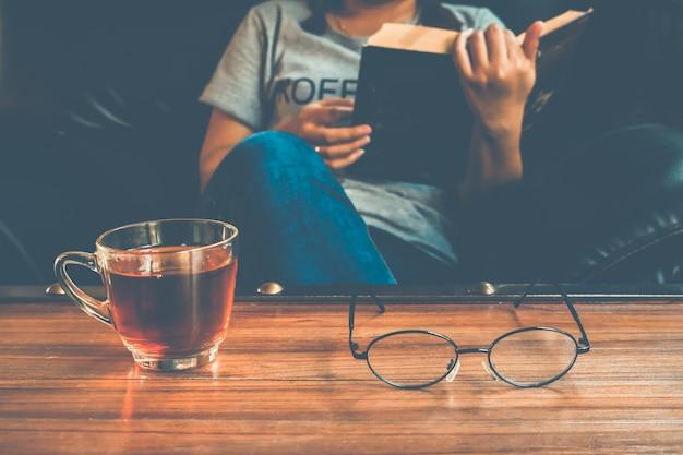 Ein glas tee auf tabelle mit frauenlesebuch auf sofa