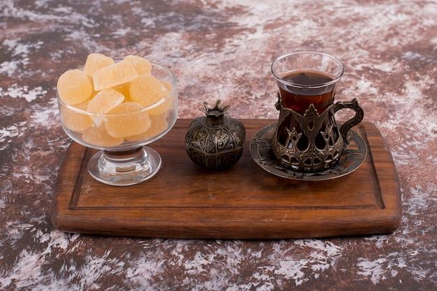 Ein glas tee in ethnischen gerichten mit marmeladen auf einer holzplatte