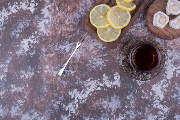 Ein glas tee mit lokum und zitronenscheiben auf einer holzplatte