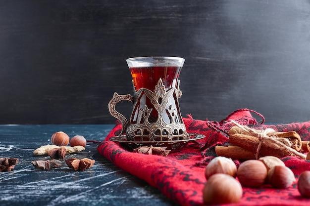 Ein glas tee mit nüssen und zimt.