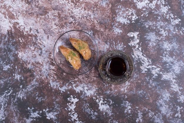 Ein glas tee mit türkischem pakhlava in der glasuntertasse in der mitte.