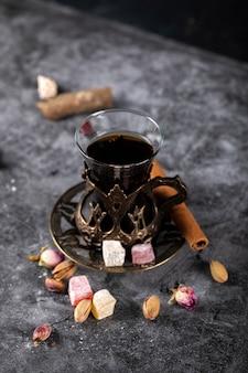 Ein glas tee, pistazien, türkisches lokum und zimt