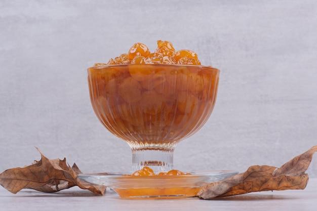 Ein glas teller mit marmelade und blatt auf weißem tisch.