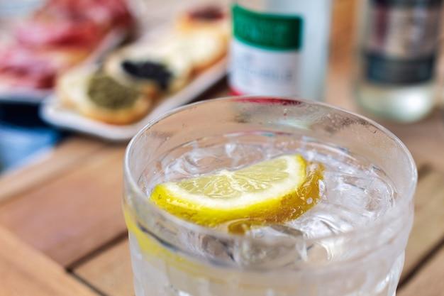 Ein glas tonic water mit zitrone und vorspeisen im hintergrund