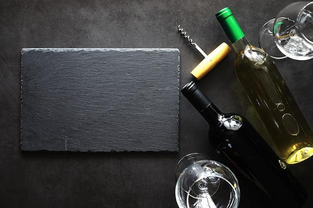 Ein glas trockener rotwein auf dem tisch. dunkle flasche und glas wein.
