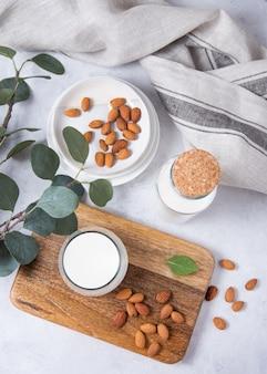 Ein glas und eine flasche vegane mandelmilch und ein paar verstreute nüsse auf weiß