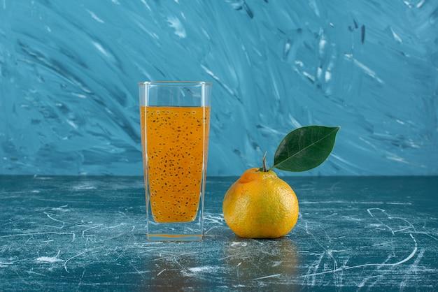 Ein glas verarbeiteten saft und grapefruit auf dem blauen hintergrund. hochwertiges foto
