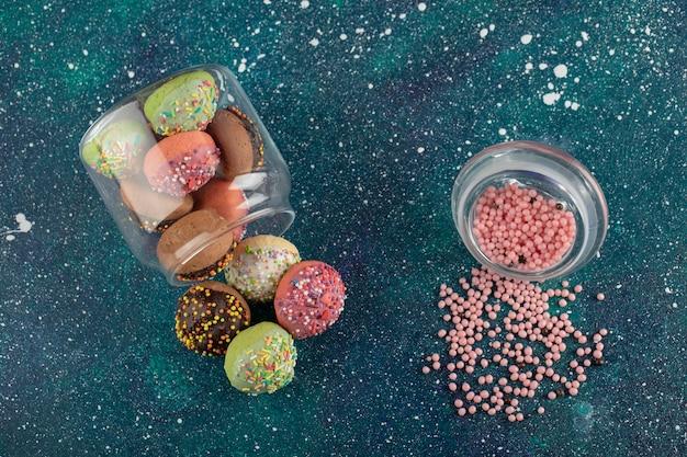 Ein glas voller kleiner bunter donuts.