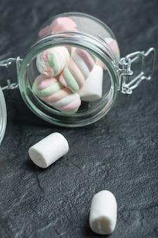 Ein glas voller marshmallows auf einer dunklen oberfläche.