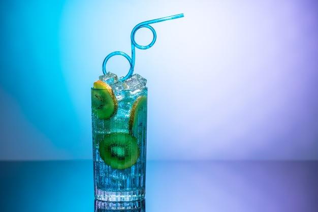 Ein glas wasser mit eis und kiwischeiben, die auf einem spiegeltisch im neonlicht stehen Premium Fotos