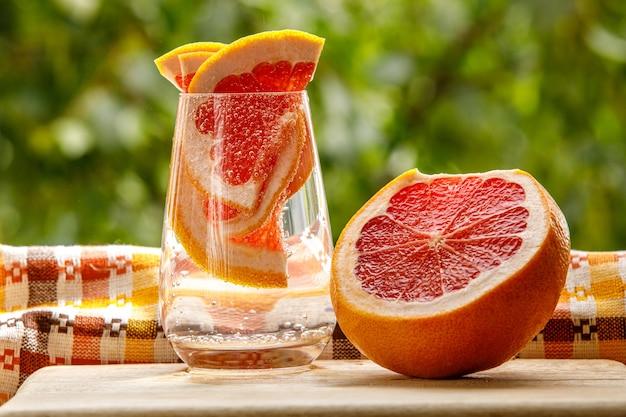 Ein glas wasser mit grapefruit im gartenhintergrund.