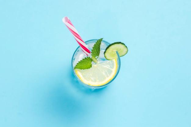 Ein glas wasser oder getränk mit eis, zitrone, gurke und minze auf blauem grund. das konzept von heißem sommer, alkohol, kühlendem getränk, durstlöschung, bar. flache lage, draufsicht