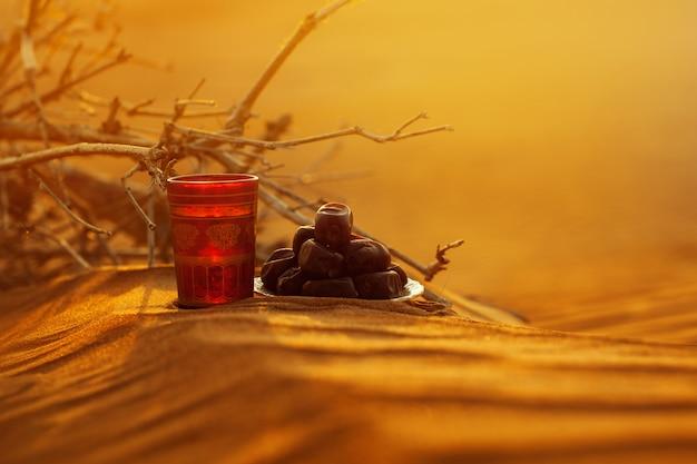 Ein glas wasser und datteln stehen auf dem sand mit blick auf einen wunderschönen sonnenuntergang.